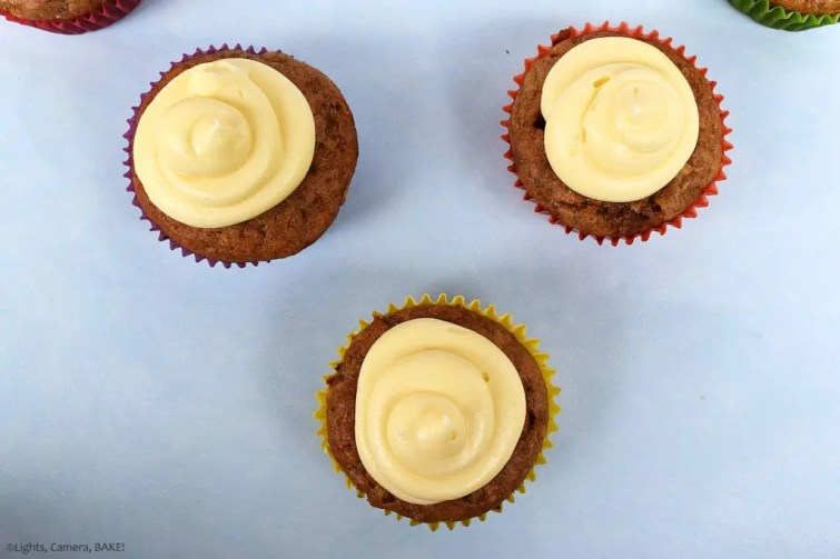 Raspberry Banana Cake Cupcakes with Cream Cheese Icing. Overhead shot of three cucpakes