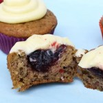 Raspberry Banana Cake Cupcakes with Cream Cheese Icing chopped in half with the raspberry jam filling