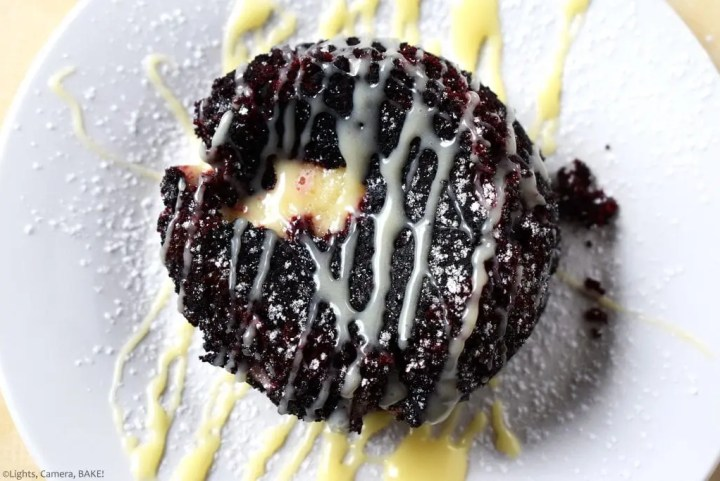 Red Velvet Lava Cake with a gooey cream cheese center, a white chocolate drizzle and a dusting of icing sugar on a white plate. Perfect for Valentines Day