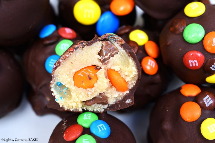 M&M Cookie Dough Truffles uses homemade cookie dough filled with chocolate chips, M&Ms and mini M&Ms. We then turn them into truffles by coating them in chocolate. #cookiedoughtruffles #cookiedoughrecipe #mandmcookiedough #mandmcookies