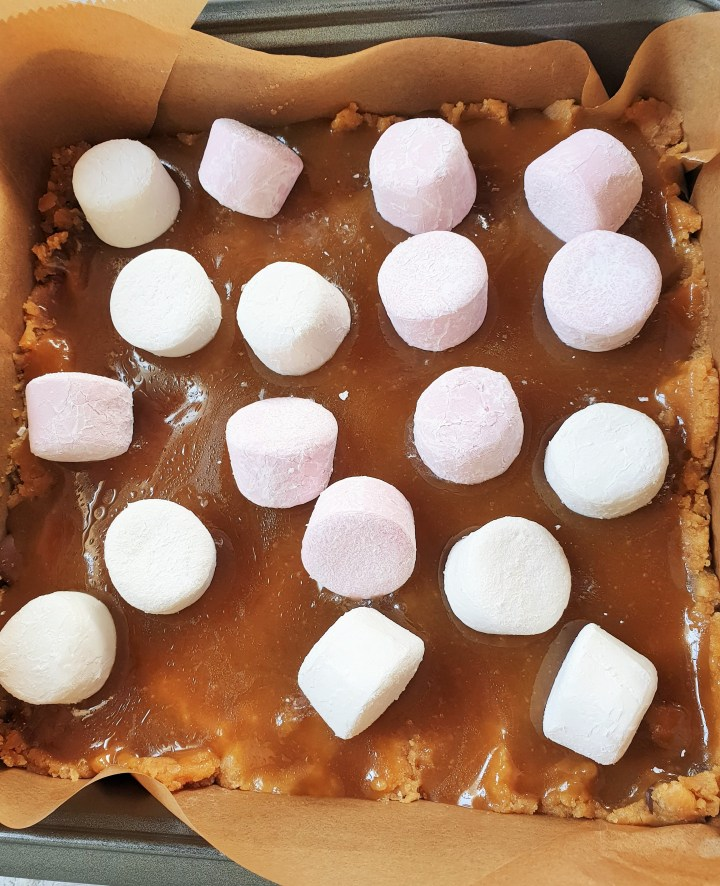 layers of peanut butter cookie dough, caramel sauce and marshmallows in a square baking pan