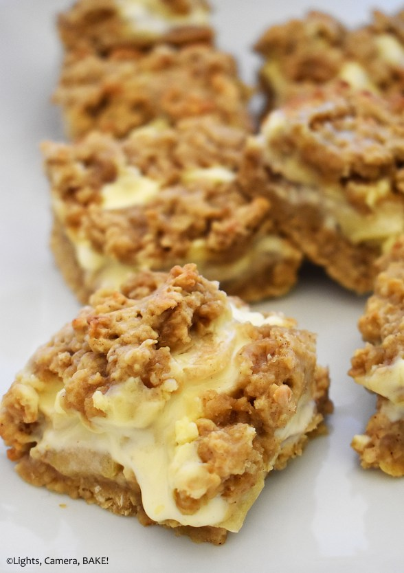 Many pieces of apple cheesecake bars on a white plate.