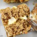 Close up of cheesecake crumble bars on a white plate.