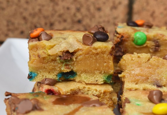 Slices of M&M caramel cookie bars with a brick background on a white plate.