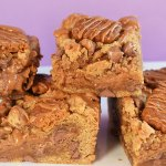 Slices of Biscoff cookie bars on purple background.