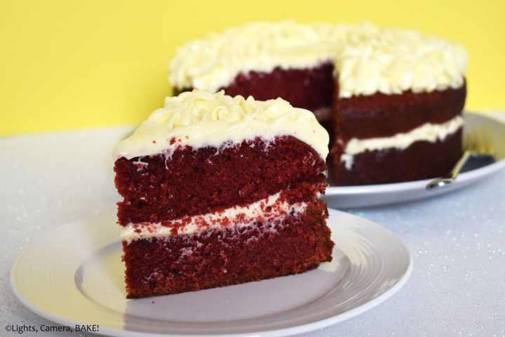 Slice of red velvet cake on a yellow background.