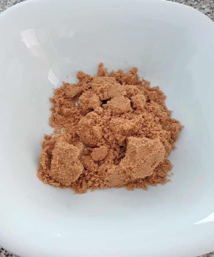 Brown sugar in a white bowl.