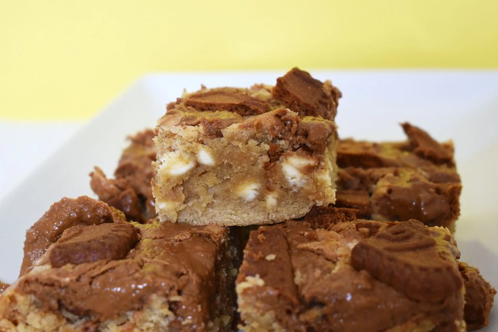 Biscoff blondies in a pile on a plate.