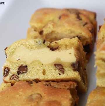 Caramilk cheesecake filled cookie bar slice on a plate.