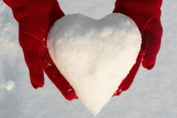 Two red gloved hands holding snow in the shape of a heart