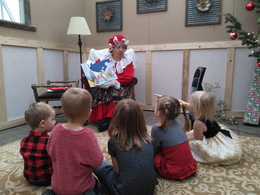 Mrs Claus reading to happy kids