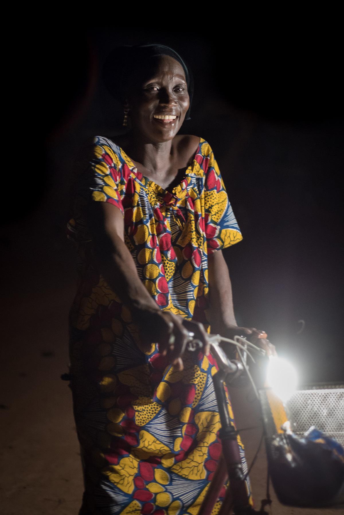 Lampe solaire Kalo 1500 et femme avec un vélo - Fabricant : Lagazel © Nicolas Remene
