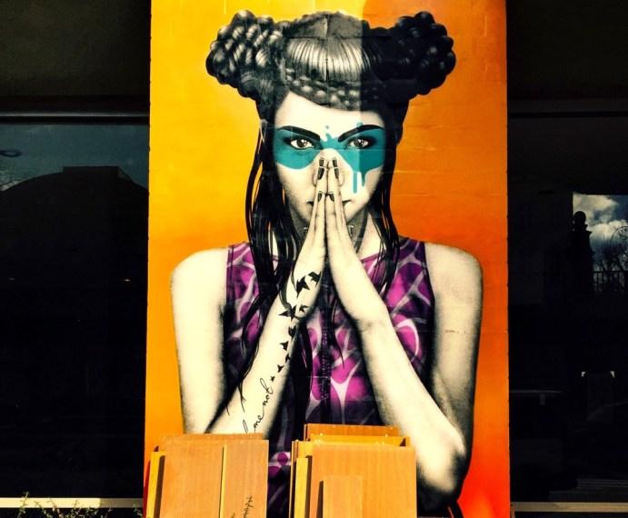 A imagem mostra a foto de um grafite feito pelo artista Finnbarr Dac, que mostra uma mulher com uma palma da mão de encontro à outra, em posição medidativa. Ela usa penteado e maquiagem bem exóticos, mas belíssimos.