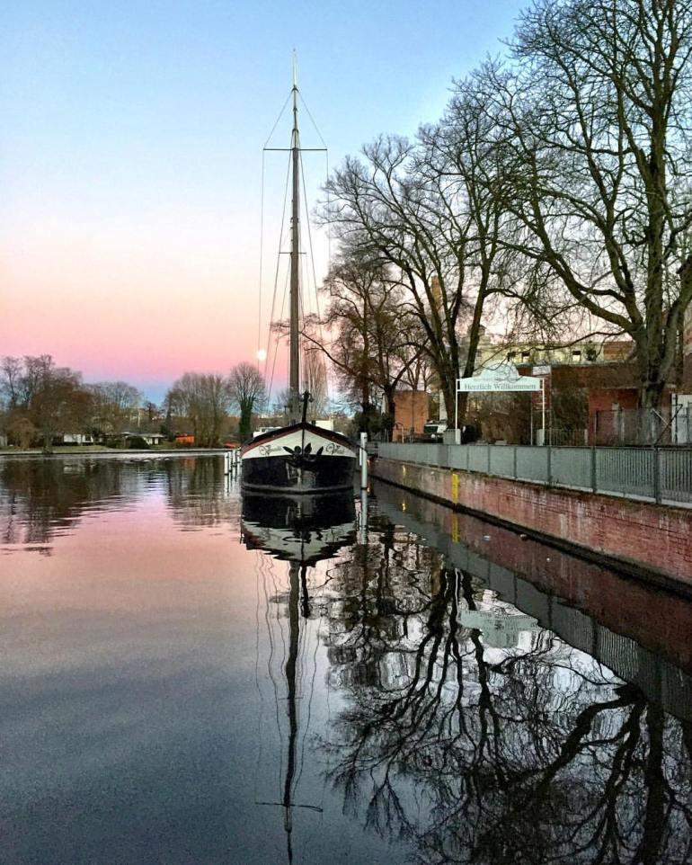 #paracegover A imagem mostra um barco a vela refletido na água na hora do crepúsculo. O céu vai do azul intenso, passando pelo laranja e chegando em vários tons de rosa. Se olhar com atenção, é possível perceber a lua atrás do mastro. — at Berlin Köpenick Spree Ufer.