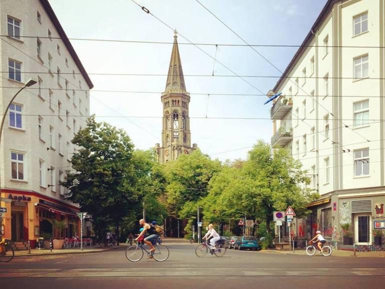 #paracegover Descrição para deficientes visuais: a imagem mostra um cruzamento com uma praça e uma igreja ao fundo. Na rua larga recortada com os trilhos do tram, passam bicicletas apressadas. — at Zionskirchstraße.