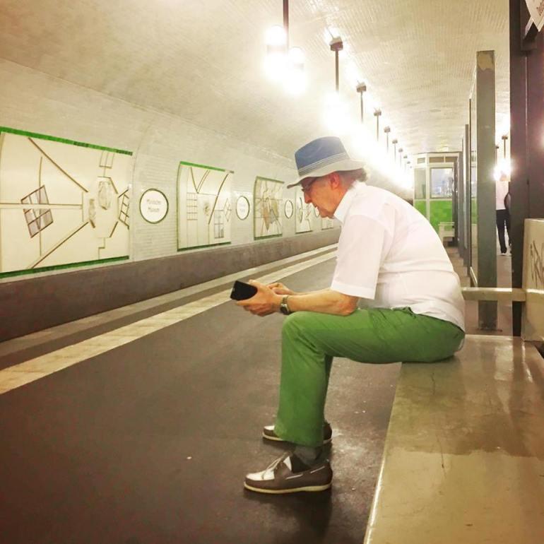 #paracegover Descrição para deficientes visuais: a imagem mostra um senhor cheio de estilo sentado no banco de madeira da estação de metrô, futucando seu celular. Ele usa camisa branca, calça verde-bandeira, mocassins bicolores e um chapéu de tecido. — at Märkisches Museum (Berlin U-Bahn).