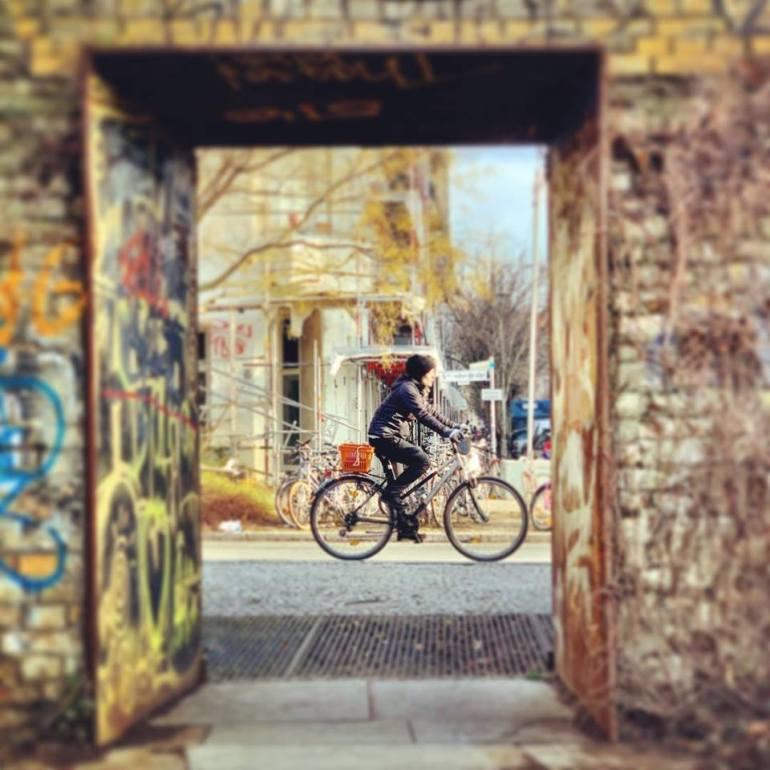 #paracegover Descrição para deficientes visuais: a imagem mostra um ciclista passando na rua visto de um portal. — at Schwedter Nordwand im Mauerpark.