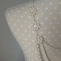 Close up image of detail on Lilly Dilly's bespoke pearl back drape jewellery draped on a polkadot dressmakers mannequin