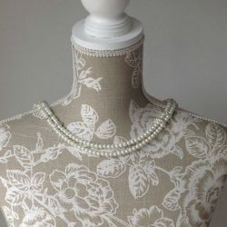 Front detail image of Lilly Dilly's bespoke pearl back drape jewellery draped on a floral dressmakers mannequin