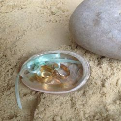 Image of Lilly Dilly's shell ring holder with 2 gold wedding rings inside tied with blue ribbon next to a pebble on the sand