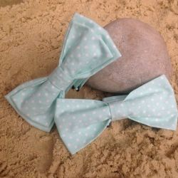 Image of two Lilly Dilly's pale blue polkadot bowties resting on a pebble on the sand
