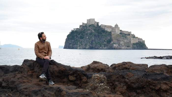 Marituccio exploring the seaside in Ischia Ponte with the Castello Aragonese in the background
