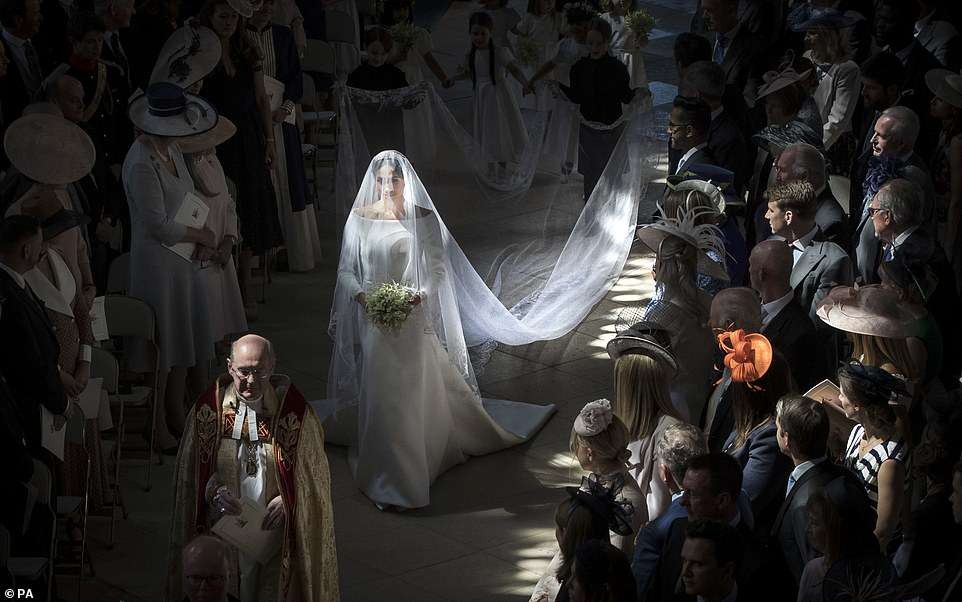 This stunning shot of Meghan Markle illuminated by sunlight as she walks down the aisle at St George's Chapel is crowned best royal photo of the year