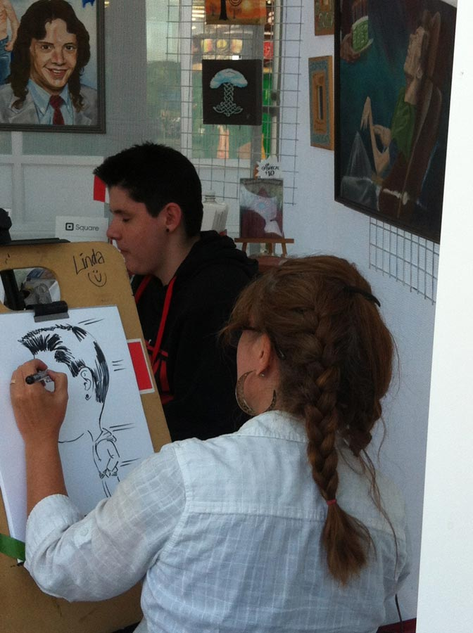 artist drawing a caricature at a summer festival