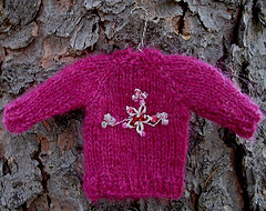 decluttering as art - miniature hand knit sweater in magenta