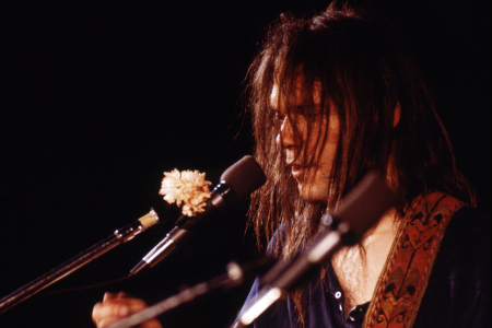 Neil Young with white carnation on his microphone during encore on Time Fades Away tour, unknown location, March 1973