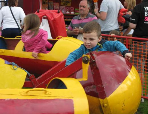 Small child enjoying a fairground rocket ride