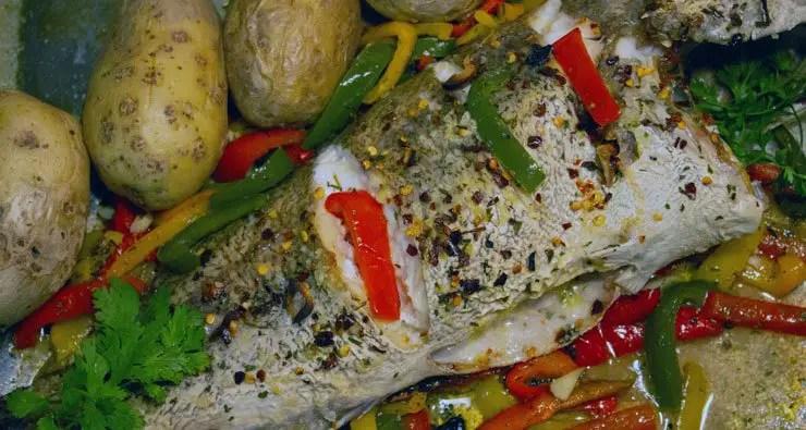 Un poisson entier rôti avec de l'huile, de l'ail et des épices entouré de poivrons tricolores.