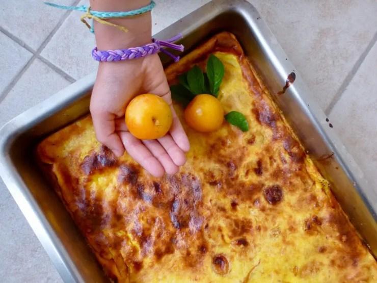 Plat de clafoutis aux prunes jaunes du jardin avec une petite main
