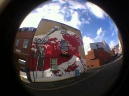 wave of kanagawa and a stiltwalker in graffiti
