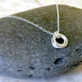 silver spiral necklace on a rocks