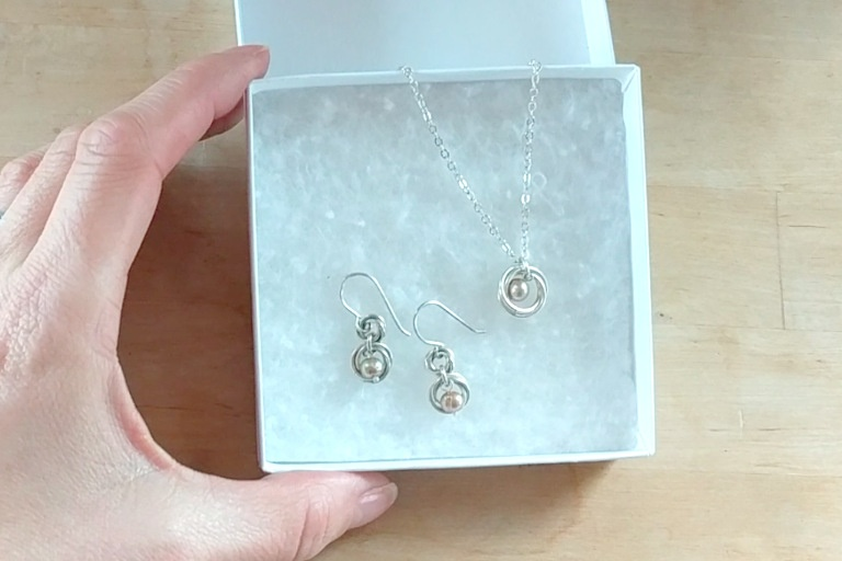 hand holding gift box with pink and silver freshwater pearl earring necklace set