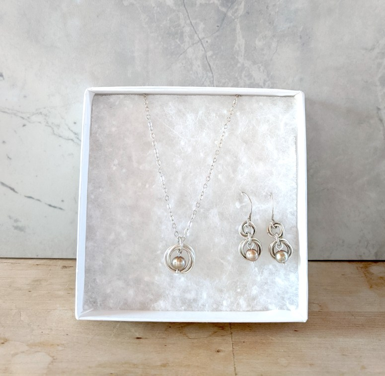 white gift box with matching silver and pearl earrings and necklace