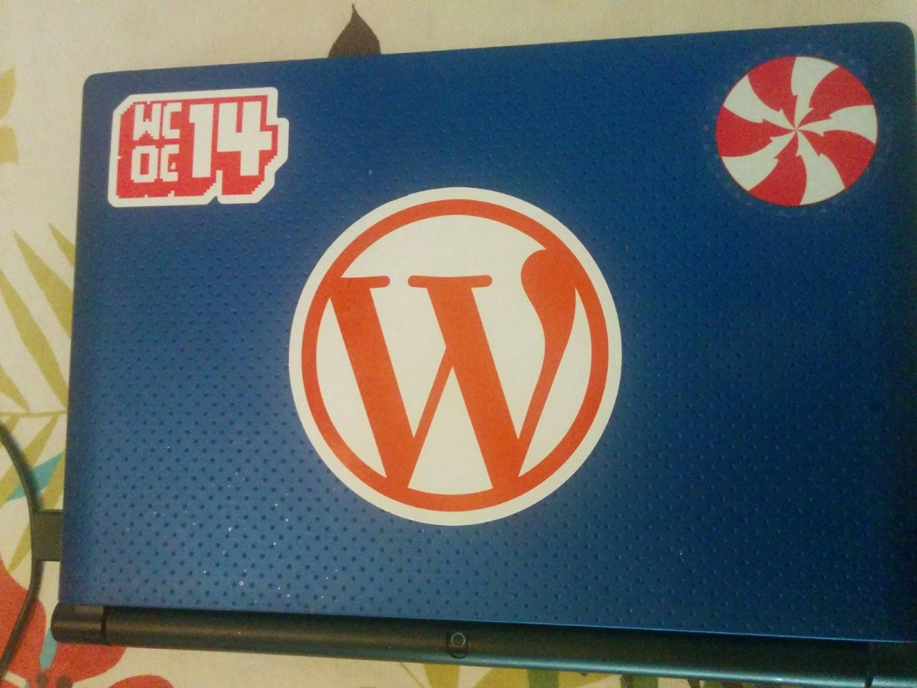 The blue shell along with a Wordcamp OC 2014 Sticker, WordPress Sticker and the Peppermint Logo prior to version 7.