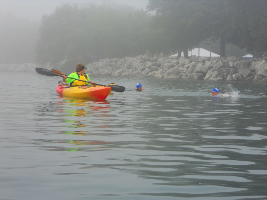 Kayaker Connie R. escorts two swimmers toward the exit ramp.