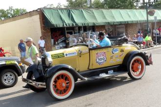 yellow two-door Ford Model A with whitewall tires and running boards