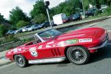 1965 red Chevrolet Corvette convertible with the top down, covered in race stickers