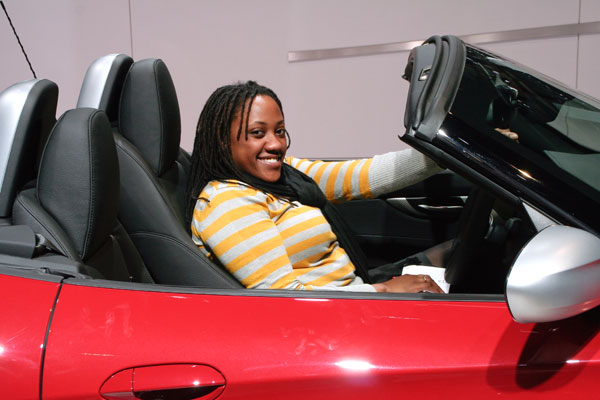 one of the women in our group looking amazed to be in the drivers's seat of the red Ferrari