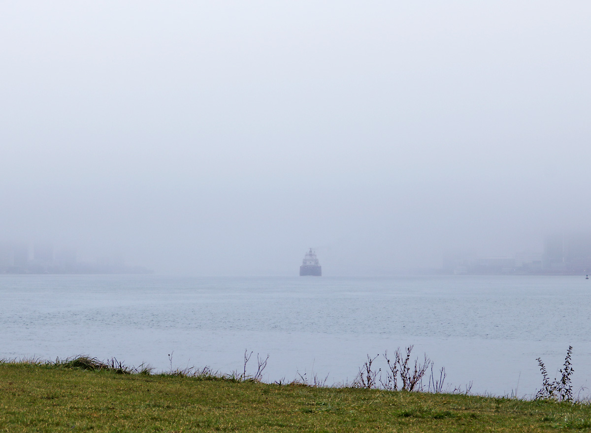 ship traveling on the river as fog appears to engulf it