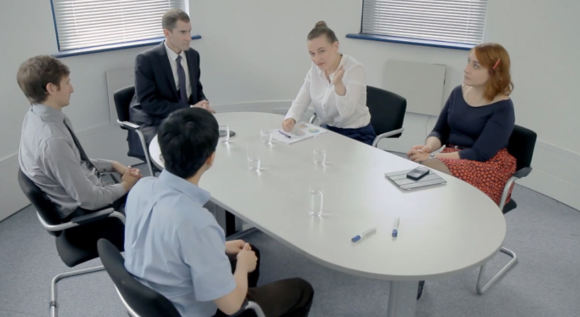 Two women and three men in a sit-down meeting discussing company initiative