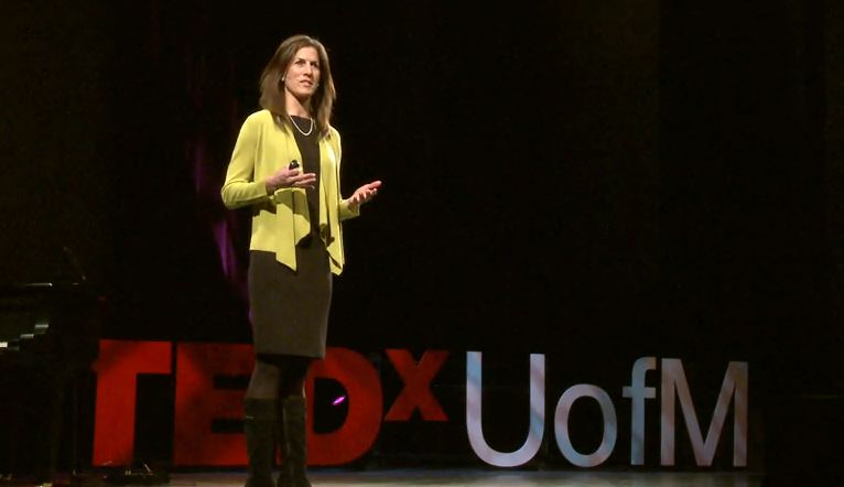 Professor Anne Curzan speaking on stage at TEDxUofM 2014