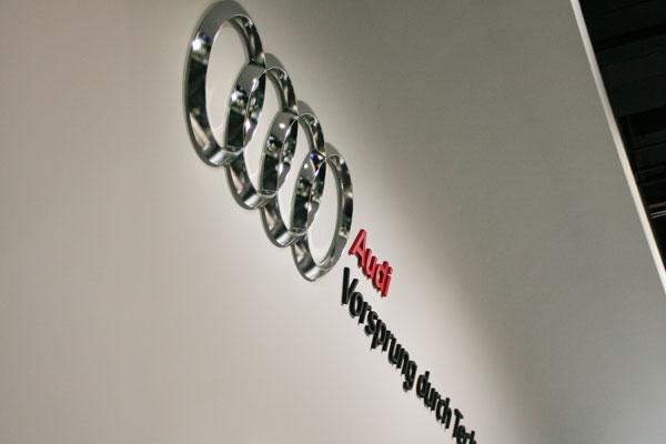 Audi emblem of intertwined circles on white wall.