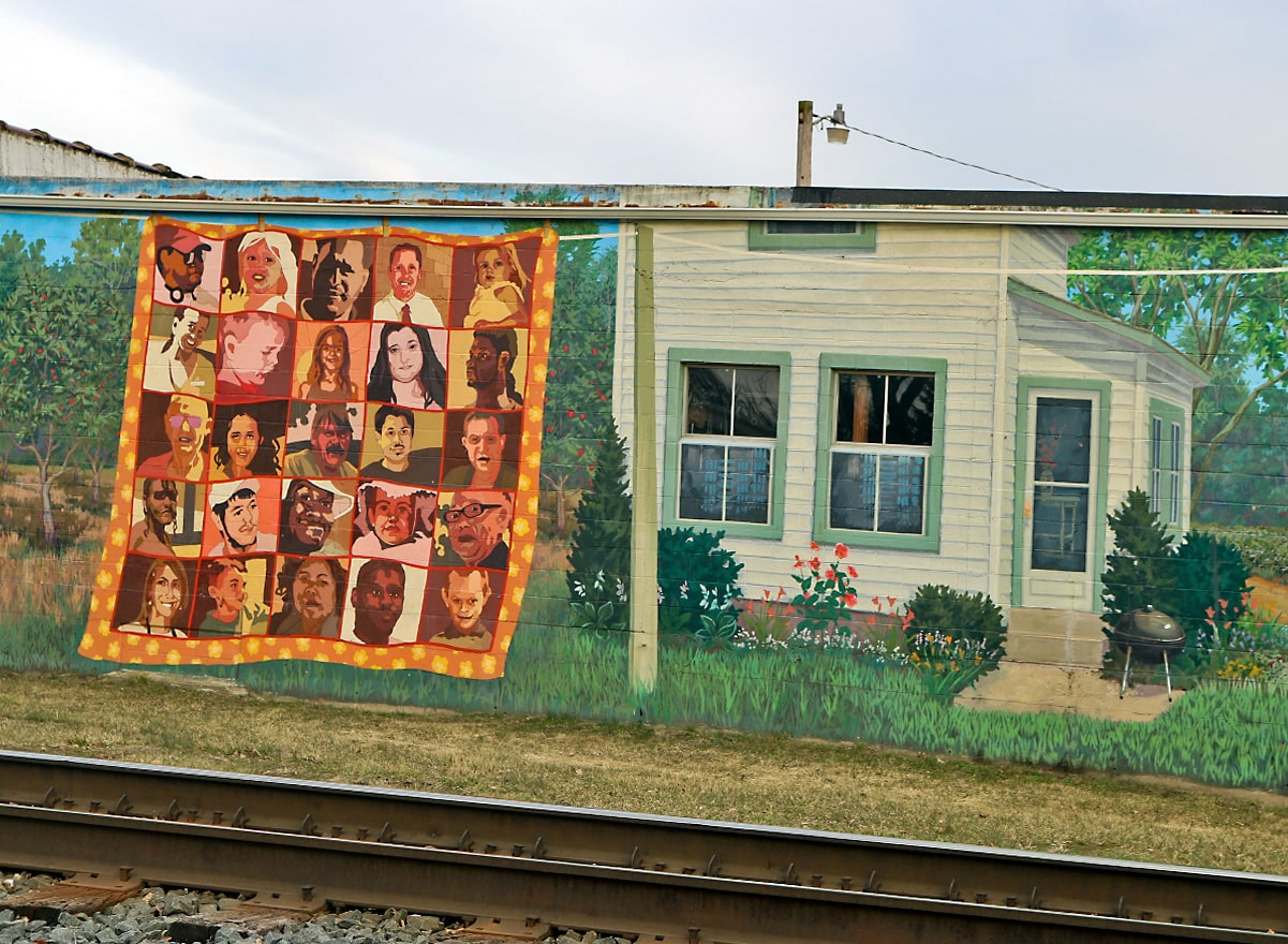 two mural panels show a quilt hanging on the clothesline in the yard with people's portraits as well as the white house with grassy lawn and carefully trimmed landscaping.