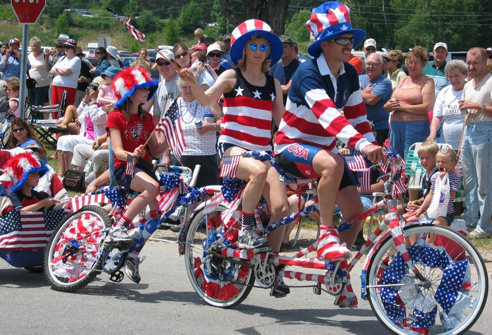 Family of four and their bikes, dressed up in red, white, and blue bicycling in 4th of July parade