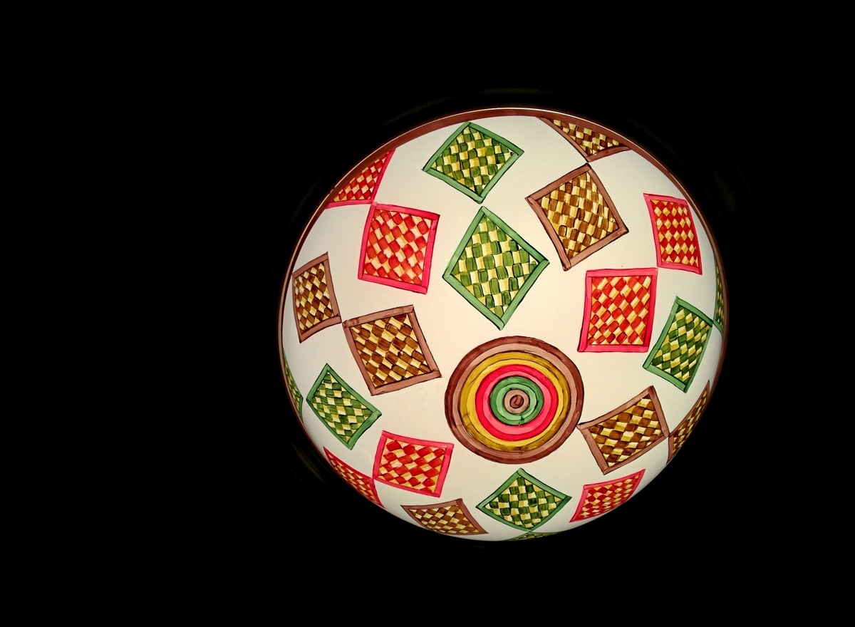 red, green, and yellow woven squares cover a white overhead light with centered circle of multiple brilliant colors.