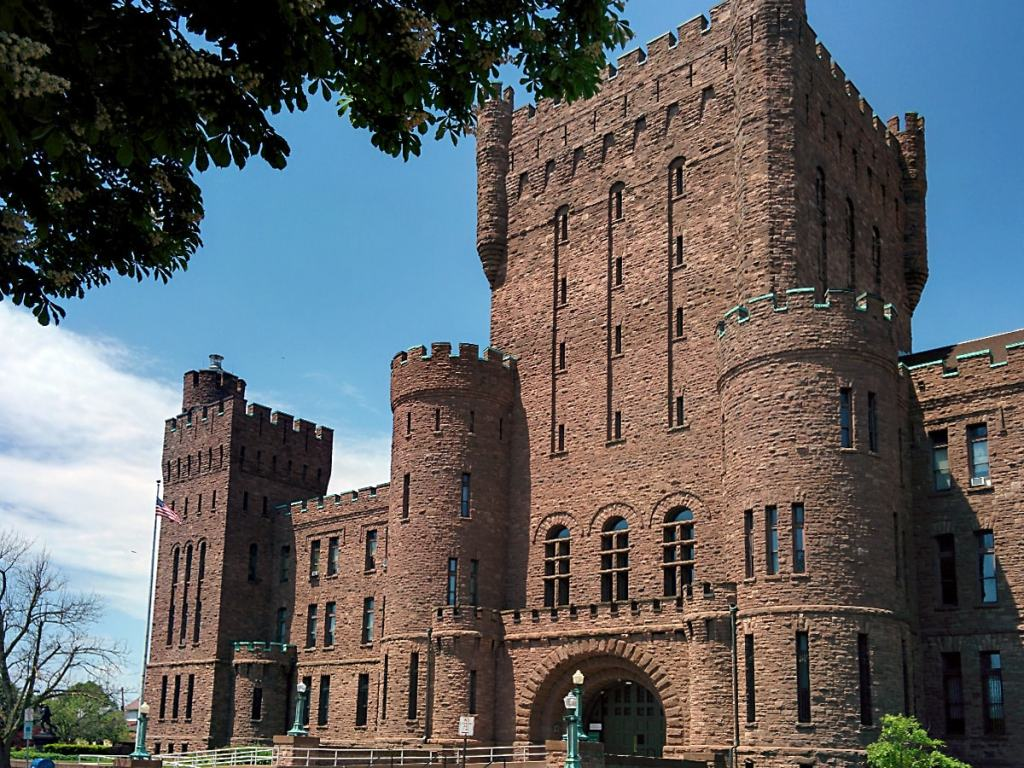 red sandstone castle-like structure of the Connecticut Street Armory, framed with blue sky and green leaves of tree branches
